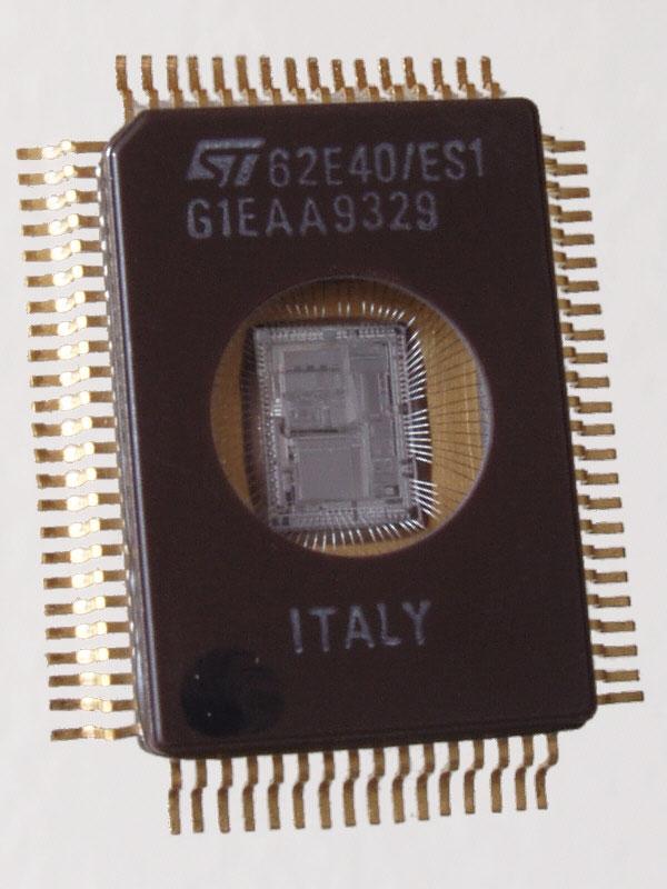 Микроконтроллер 1993 года с УФ стиранием памяти 62E40 европейской фирмы STMicroelectronics. За окошечком виден кристалл микросхемы — кремниевая подложка с выполненной на ней схемой.